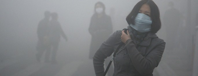 A woman wearing a mask walk through a street covered by dense smog in Harbin, China.